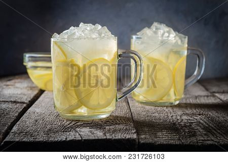 Two Cups Of Lemonade And Ice Cubes Crumbs On A Wooden Table Background Natural Lemon Water Food Soda