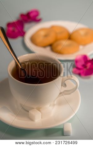 A Cup Of Tea On The Table. Tea With Shortbread Cookies. Black Tea On The Table Is Decorated With Flo