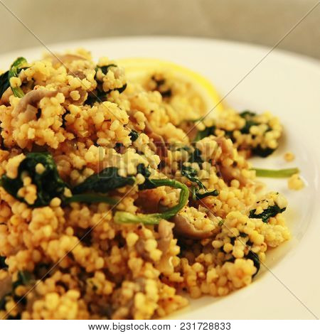 Millet With Mushrooms And Spinach. Jewish Cuisine. Vegetarian Couscous On The Round White Plate. Clo