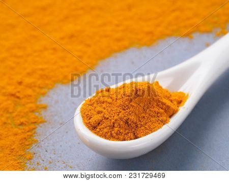 Turmeric Powder Or Curcuma Longa And White Spoon With Turmeric Powder On Gray Background. Copy Space