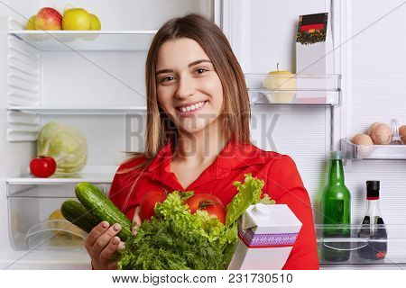 Satisfied Woman Holds Fresh Vegetables And Milk, Going To Put Them In Refridgerator, Has Broad Smile