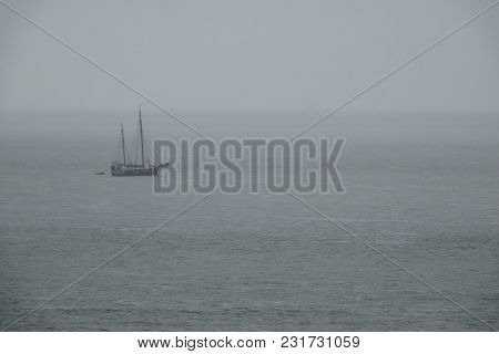 An Ancient Sailing Ship In The Sea In Cloudy Foggy Weather.
