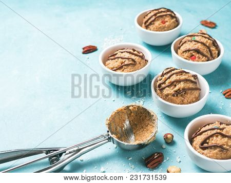 Safe-to-eat Raw Monster Cookie Dough In Small Portion Bowl, Ice Cream Scoop And Nuts On Blue Backgro