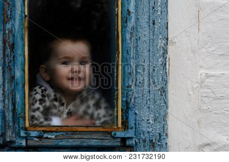 A Little Girl Sits In An Old Hut On A Window On Which The Paint Faded 2018