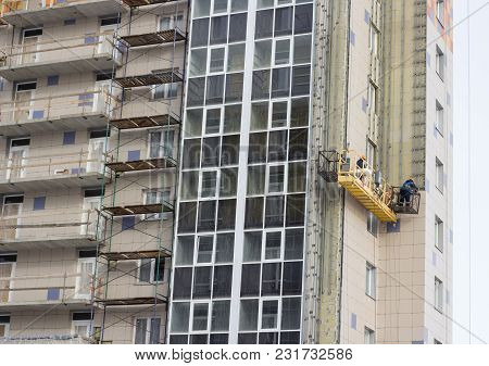 Construction Decoration Work Of The Facade By Builders In A Construction Cradle Of New Residential B