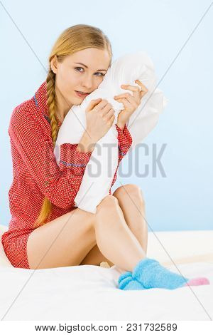 Bedding Fabric Softener Concept. Young Woman Wearing Cute Pink Pajamas Hugging Soft Pillow