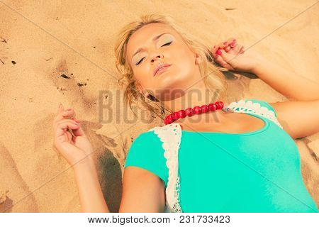 Holidays Relax Time Concept. Blonde Woman Lying On Sand. Lady Has Big Necklace. Female Is Chilling O