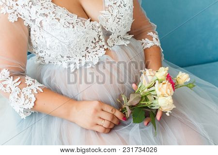 Pregnant Woman In A Beautiful Dress With Bouquet Of Roses.