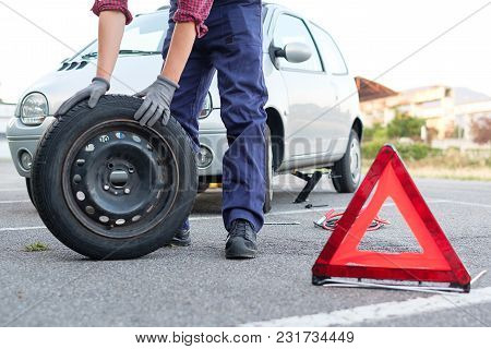 Man Changing A Flat Tyre After Vehicle Breakdown