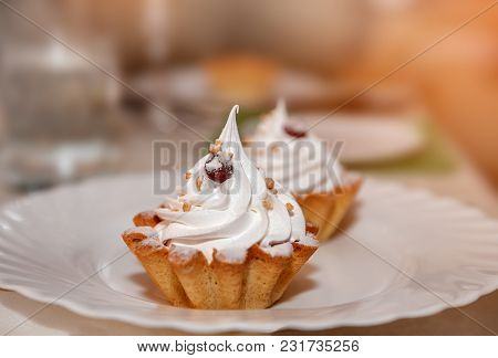 Appetizing Baked Basket With Lemon Mousse And Whipped Cream, Whipped Egg Whites. Food On A White Pla