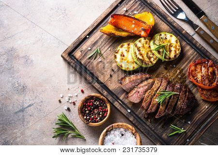 Grilled Beef Steak And Grilled Vegetables On A Wooden Serving Board. Barbecue Dish. Top View With Co