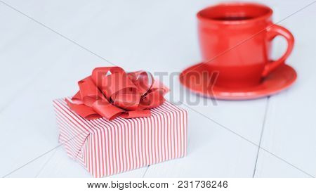 Close-up Background Image Of Red Cup And Gift Box On Light Background.photo With Place For Text