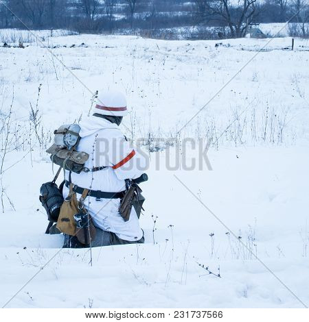 Soldier In White Camouflage Has Taken A Sitting Position On The Battlefield Concept Of War