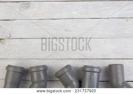 Assorted Pvc Sewage Pipe Fittings Shot On The Wooden Background. Top View. Copy Space For Text