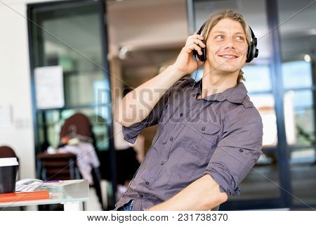 Young man in the office with headphones