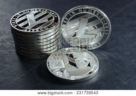 Column Of Litecoins With Two Single Coin Next To Them On Dark Leather Surface. Virtual Crypto Curren