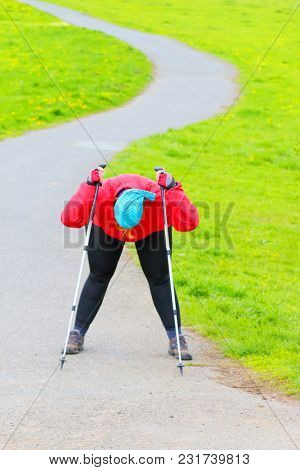 Tired nordic walker relaxing. Overweight woman enjoying life on spring meadows. Healthy lifestyle concept.