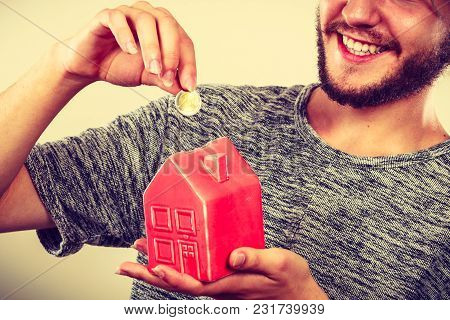 Household Savings And Finances, Economy Concept. Smiling Man Putting Money Coin Into Piggy Bank In S