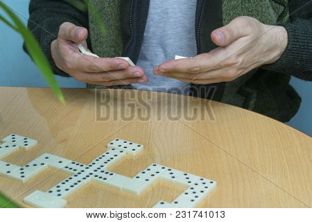A Man In A Dark Green Wool Cardigan Plays Dominoes At A Table Next To An Indoor Plant, Holding The D
