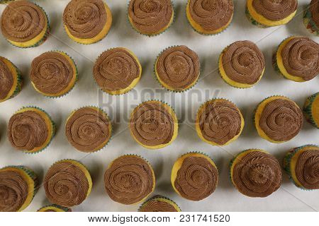Delicious Handmade Vanilla Cupcakes With Homemade Chocolate Butter Cream Frosting Sitting On Parchme