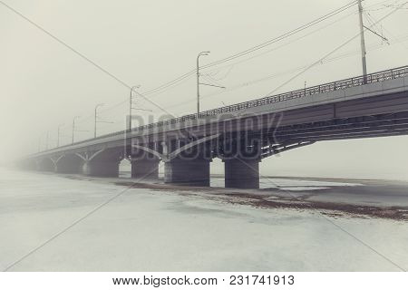 Bridge In Fog Over Frozen River In Ice And Snow. Mysterious Urban Landscape With Mist In Foggy Day,