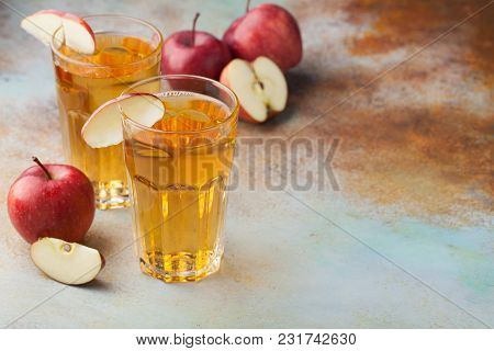 Two Glasses Of Red Apple Juice With Mint And Ice On An Old Rusty Table. Soft Drink On A Blue Backgro