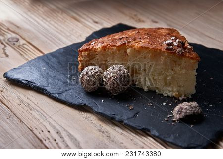 A Piece Of Apple Pie With Grated Chocolate Near Chocolate Truffle Candies.