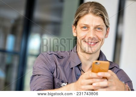 Confident young man in smart casual wear holding phone