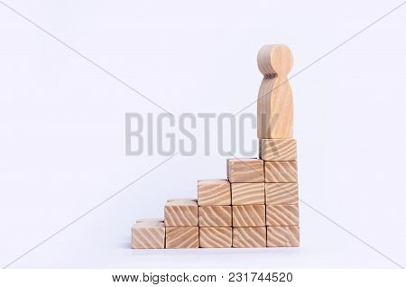 A Wooden Man Stands At The Top Of A Social Or Career Ladder. Concept Of Business Success. Stairs Of