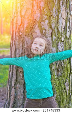 The Little Girl Embraces A Big Tree Playing Outdoors In Summer. Happy Childhood