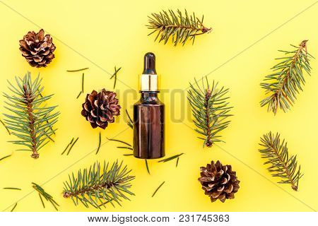 Pine Essential Oil In Bottles On Yellow Background Top View Copy Space. Pattern With Pine Branch And