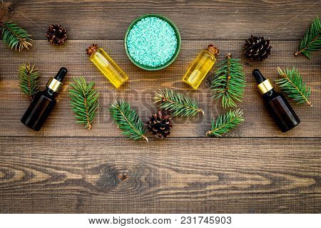 Pine Essential Oil In Bottles On Wooden Background Top View Copy Space. Pattern With Pine Branch And