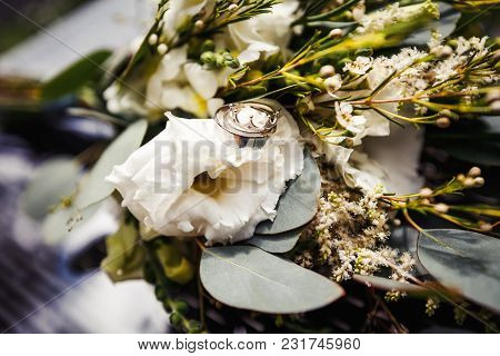 Gold Wedding Rings On A Bouquet Of White Flowers