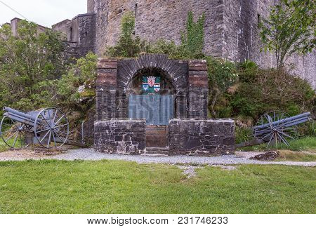 Dornie, Scotland - June 10, 2012: Historic Artillery Pieces With Ww1 War Memorial Outside Wall Of Ei