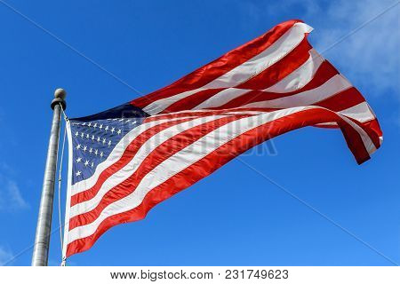Usa Flag Waving Against Clear Blue Sky On Bright Sunny Day.