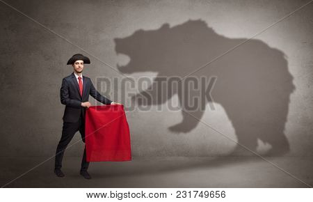 Businessman standing with red cloth in his hand and big bear shadow on his background