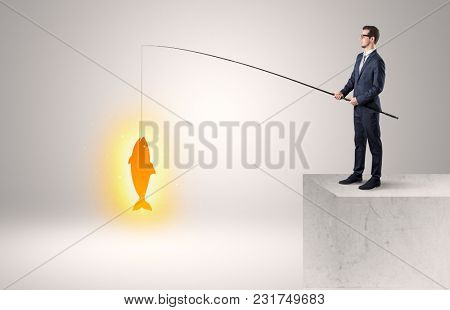 Young businessman fishing golden fish from the top of a building