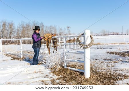 Horizontal Image Of A Middle Aged Caucasian Cowgirl Standing By Her Saddle Tying String On It While