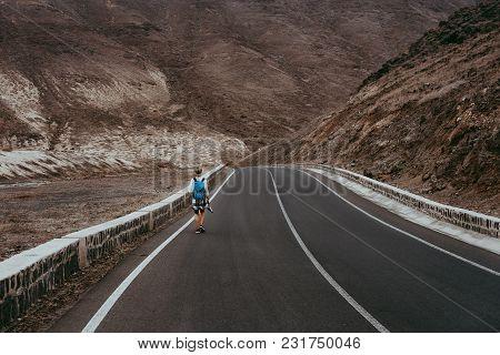 Traveler Woman With Backpack Walks On Empty Road Among Rocky Volcanic Landscape Huge Volcanic Mounta