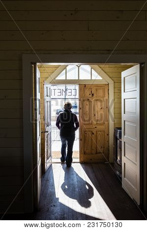 Vertical Image Of A Woman Creating A Silhouette And Shadow In The Doorway As She Is Walking Out.