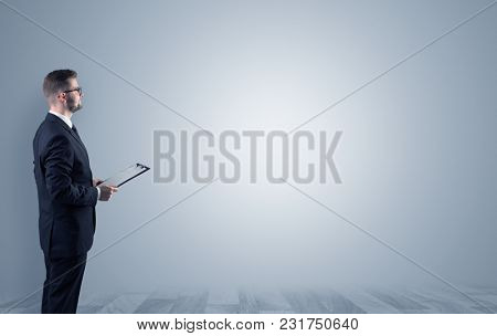 Elegant businessman standing and presenting something in an empty space with floor