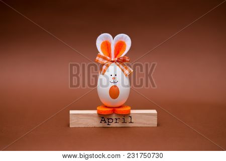 Multicolored Funny Eggs In The Form Of Cute Bunny With Wooden Calendar Set On April Isolated On Brow