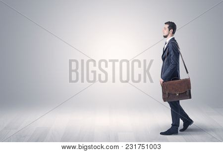 Successful businessman walking in front of an empty wall with briefcase on his hand
