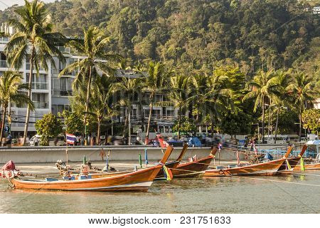 Typical Boats Of The Area On The Island Of Phuket Back You Can See A Small Beach And Buildings Near