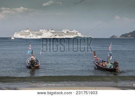Typical Boats Of The Area And Anchored Cruises In Front Of The Port Of Phuket Island Thailand