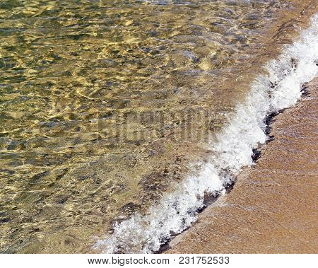 Soft Wave Rolling Onto A Sandy Shore