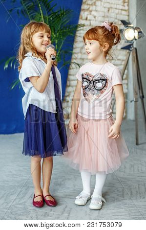 Two Young Children Sing A Song On A Microphone. Group. The Concept Is Childhood, Lifestyle, Music, S