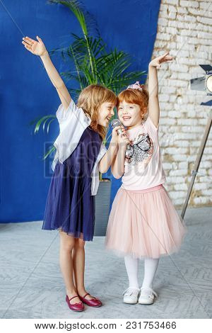Two Little Smiling Kids Dance And Sing A Song In Karaoke. The Concept Is Childhood, Lifestyle, Music