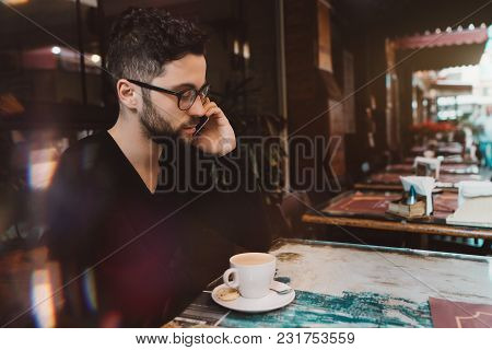 Young Handsome Serious Bearded Man Entrepreneur In Glasses Is Having Work Conversation Via Smartphon