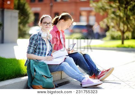 Young Happy Students With Books And Notes Outdoors. Smart Young Guy And Girl Doing Their Homework In